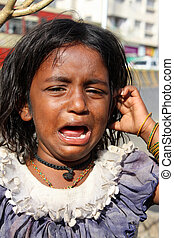 A little beggar girl from India standing on the streetside, crying for food.