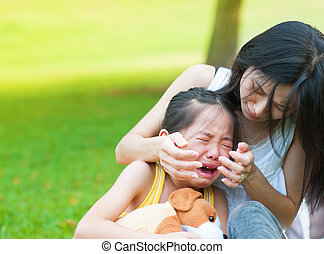 Crying little Asian girl - Asian mother is comforting her...