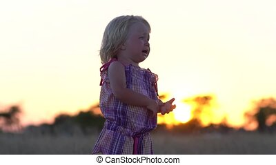 Crying little girl alone in the meadow. Child at sunset in the meadow.