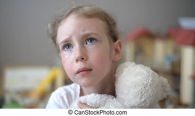 Crying little girl with bear.