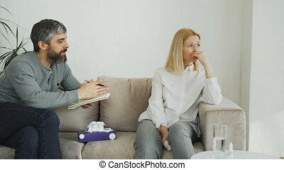 Crying stressed woman talking with professional male...