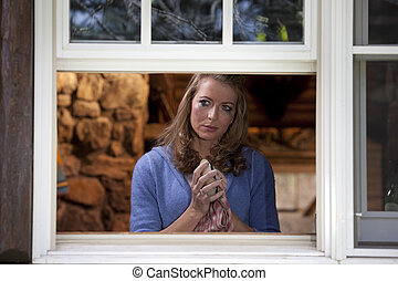 Portrait of a crying woman standing at her kitchen window and drying a dish. She is viewed from outside the window and is staring into the distance as mascara runs down her face. Horizontal format.