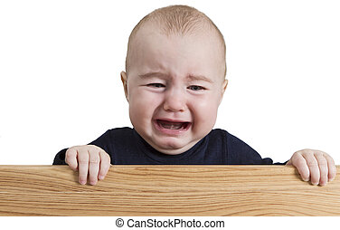 crying young child holding wooden board - crying young child...