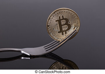 Crypto coin bitcoin in fork with reflection. Close-up.