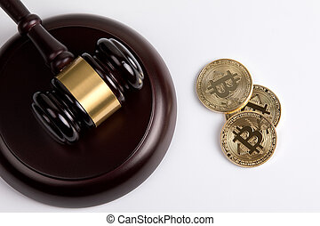 crypto currency, golden bitcoin with a wooden judges gavel on white background