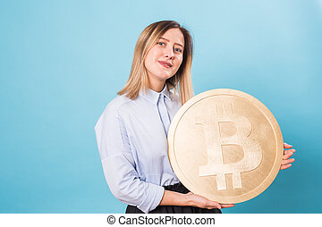 Cryptocurrency and economy concept - Young woman holds a gold bitcoin