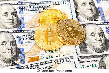 Cryptocurrency golden Bitcoin lying on the one hundred american dollar bills. Business concept of digital money