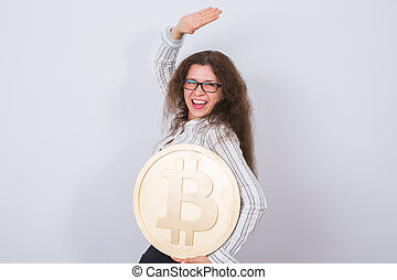 Cryptocurrency, virtual money and blockchain concept - Young funny woman holds a big gold bitcoin in her hand.