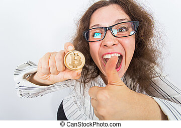 Cryptocurrency, virtual money and blockchain concept - Young funny woman holds a gold bitcoin in her hand.