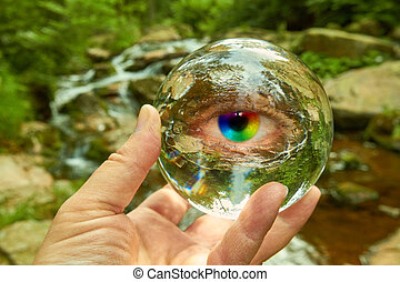 crystal ball - A hand holding a crystal ball on a creek.