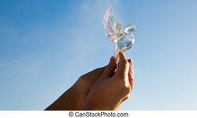 Crystal bird in the hands of a girl