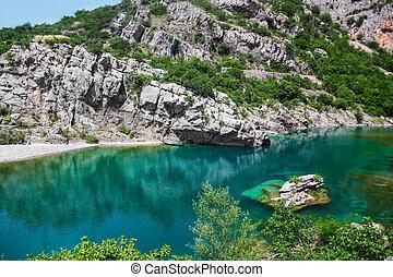 crystal blue mountain lake with rocks
