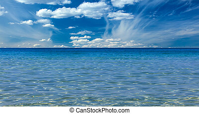 Crystal clear sea and blue sky with clouds