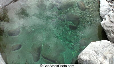 Crystal clear turquoise mountain river Verzasca flows in...