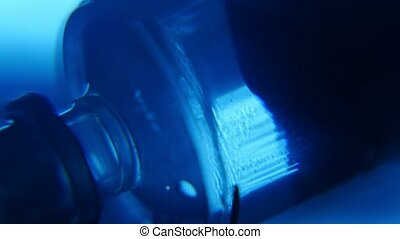 Crystal clear water is pulled in a plastic syringe in blue...