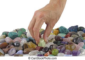 Crystal healer choosing a tumbled healing stone