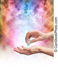 Crystal Healer holding terminated quartz in one hand pointing it at open palm with psychedelic rainbow colored energy formation in background