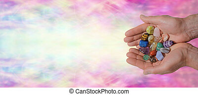 Male crystal therapist holding selection of crystals on a colorful rainbow bokeh background