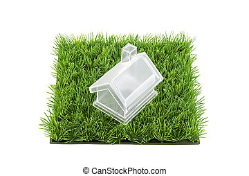 Crystal house on square of green grass field isolated on white background