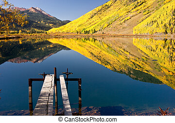 Crystal Lake in Autumn - Rocky Mountain foliage reflects in...