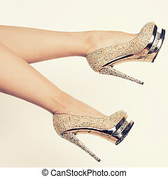 crystals encrusted gold shoes on slender female legs isolated white background