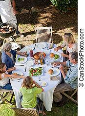 család eszik, a kertben