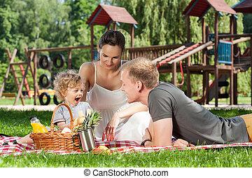 család piknikel, képben látható, a, játszótér