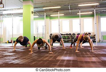 csoport emberek, doing push-ups, alatt, tornaterem