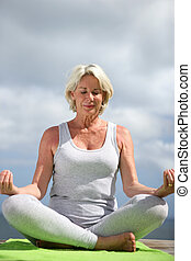cuarentón, mujer, sentado, en, posición yoga