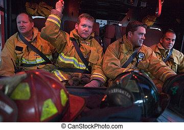 cuatro, bomberos, en, camión de bomberos, con, engranaje