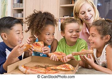 cuatro, niños jóvenes, dentro, con, mujer que come, pizza, sonriente