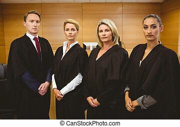 cuatro, serio, jueces, posición, mientras, llevando, batas