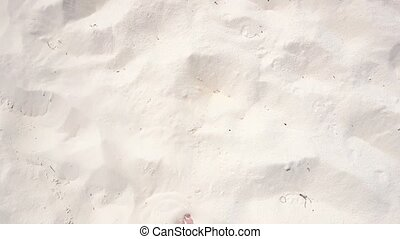 human legs, walking on the white sand beaches of the...