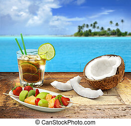 cuba libre and tropical fruit on a wooden table in a polynesian seascape