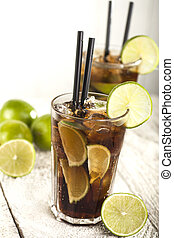 Cuba Libre Coctail with lime on a white wooden background