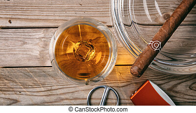 Cuban cigar and a glass of cognac brandy on wooden background, top view