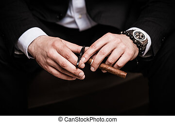Cuban cigar - elegant man wearing black suit and white shirt...