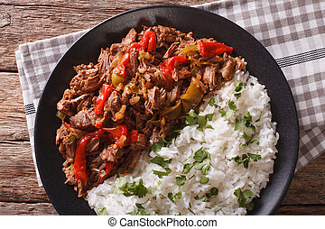 Cuban cuisine: ropa vieja meat with rice garnish closeup....