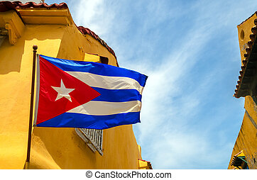 Cuban flag set against blue sky and yellow colonial buildings