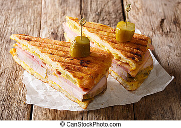 Cuban sandwich with ham, mustard, cheese, pickled and pork close-up. horizontal