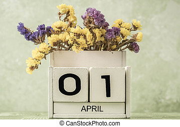 cube calendar for april on green background with copy space