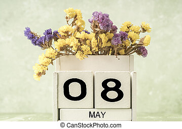 cube calendar for may on green background with copy space