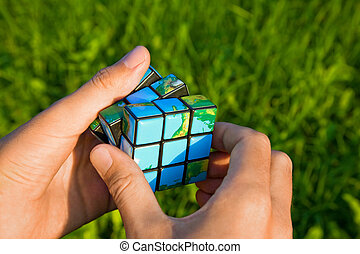 Cube in the manner of planets land in hand on background of the herb