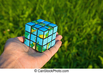 Cube in the manner of planets land on palm on background of the herb
