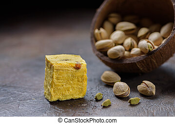 Cube of dessert soan papdi, cardamom grains, pistachios and almond on concrete kitchen surface.