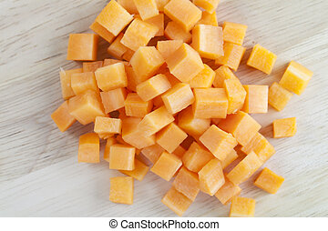 Brunoise or cubed carrots on wooden surface.