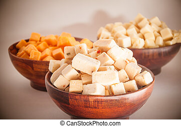 Assorted pepperjack cheddar feta and swiss cheese on wooden bowls on dining table over white background