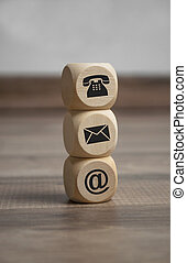 Cubes and dice with contact icons on wooden background