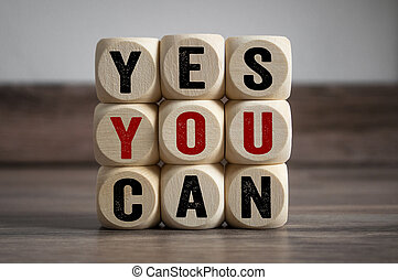 Cubes and dice with slogan Yes you can on wooden background
