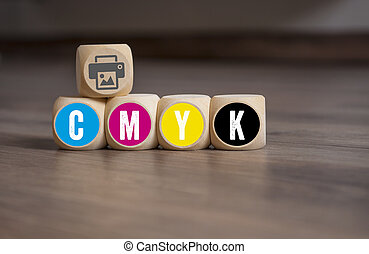Cubes dice with CMYK on wooden background
